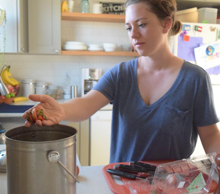 putting kitchen scraps into bucket